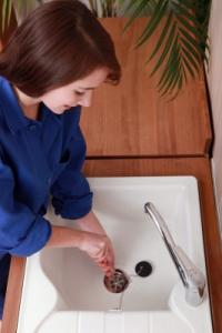 Michelle is unclogging a drain sink